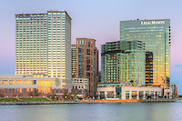 The orange colored western reflects in the windows of part of the skyline of the Harbor East development, including the Baltimore Marriott Waterfront Hotel and the Legg Mason Building at twilight in Baltimore, Maryland.