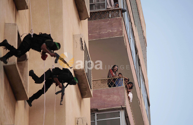 Palestinian militants of the Ezzedine al-Qassam Brigades, Hamas's armed wing, rappel down a building during an anti-Israel parade as part of the celebrations marking the first anniversary of an Israeli army operation in Gaza, on November 14, 2013. A year after trading fire in a week-long war in Gaza, in which more than 170 Palestinians and six Israelis were killed, Israel and Hamas are squaring up for another confrontation, despite both sides appearing reluctant to make the first move. Photo by Ashraf Amra