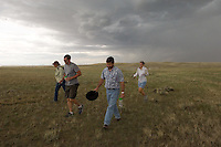 Paleontologists Kelli Trujillo, left, of the University of Wyoming, Matt Lamanna, and Chris Beard, of the Carnegie Museum of Natural History, and paleobotanist Mandi Lyon of Pennsylvania University, right, scramble to escape an approaching rain storm on a part of the Allen Cook ranch recently donated to the University of Pittsburgh for research. The ranch property features cretaceous rock formations preservibg dinosaur fossils, high-plains grassland ecology and interesting tectonic geology for study by the students and faculty of Pittsburg, the University of Wyoming and the Carnegie Museum. (photo/Kevin Moloney)
