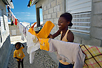 """A woman hangs laundry in a model resettlement village constructed by the Lutheran World Federation in Gressier, Haiti. The settlement houses 150 families who were left homeless by the 2010 earthquake, and represents an intentional effort to """"build back better,"""" creating a sustainable and democratic community."""