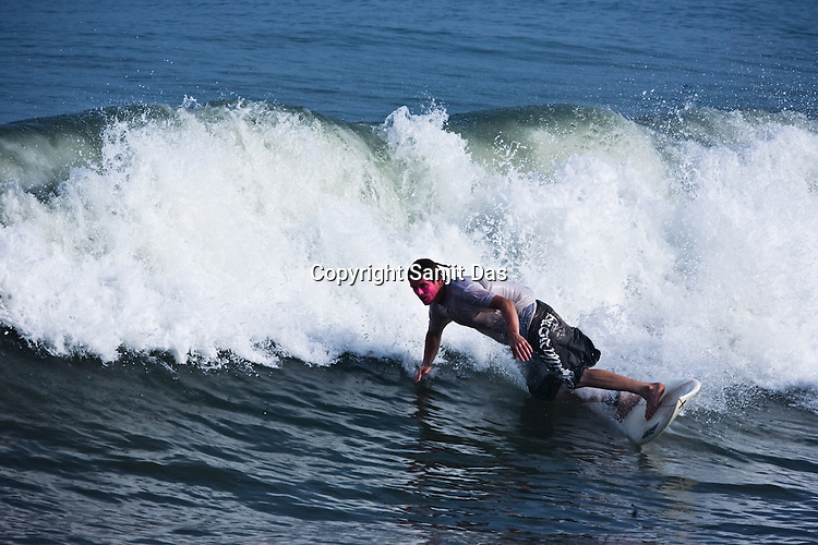 """Jeeru Krishna Dasa, one of the Krishna devotees from the Kaliya Mardana Krishna Ashram is seen surfing on the Arabian Sea on the beach front of Mangalore, Karnataka, India.  ..Krishna devotees in the Gaudiya Vaishnava tradition of Hinduism, they are known collectively as the """"surfing swamis."""" The """"surfing ashram"""" is growing in popularity and surfing here is a form of meditation, a spiritual practice leading to heightened states of awareness."""