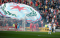 The Chicago Fire celebrate after scoring a goal as the fans unfurl a large banner.  The Chicago Fire defeated the New York Red Bulls 3-1 at Toyota Park in Bridgeview, IL on April 7, 2013.