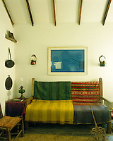 Hand-woven Irish wool rugs are thrown over a simple wooden settle at one end of the sitting room