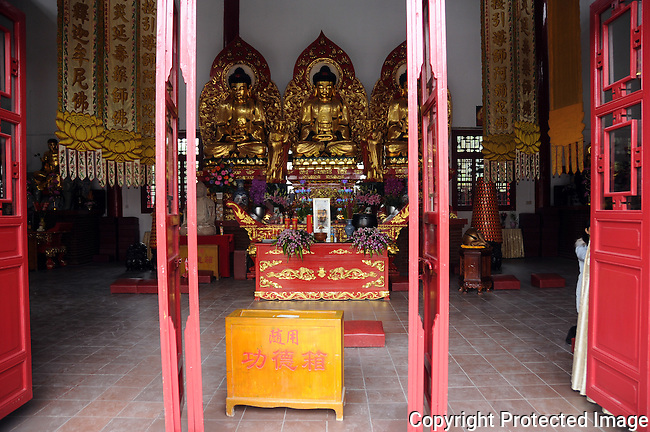 gold statues at wall, fruit and flower offerings on altar before them, in the interior of a Buddhist temple, Guilin, China