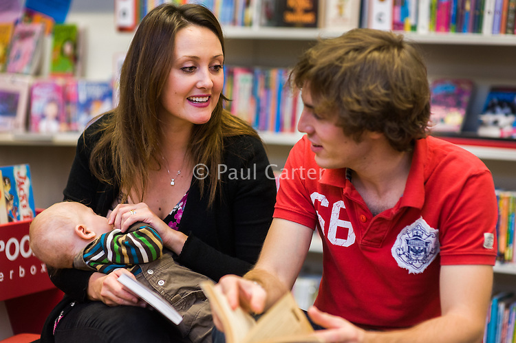 A young woman breastfeeds her baby in a library while searching for and reading books with her husband.<br /> <br /> 11 November 2011<br /> Hampshire, England, UK