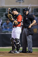 Kannapolis Intimidators catcher Nate Nolan (22) puts on his mask as home plate umpire Mike Rains looks on during the game against the Lakewood BlueClaws at Kannapolis Intimidators Stadium on April 8, 2017 in Kannapolis, North Carolina.  The BlueClaws defeated the Intimidators 8-4 in 10 innings.  (Brian Westerholt/Four Seam Images)