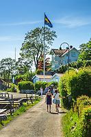 Människor promenerar  på grusväg på Dalarö strandväg i Stockhjolms skärgård.