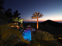 The swimming pool and surrounding terraces are illuminated to dramatic effect at night