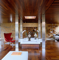 In the living area a white marble-topped table in the shape of a cross and surrounded by four steel pillars is lit from above by a skylight