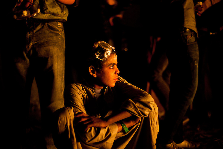 A boy watches protestors battling police in betwen barrages of tear gas and rubber bullets on Mohamad Mohamad street after a truce between the police and protestors was broken. Street battles raged around the heavily fortified Interior Ministry, near Tahrir square, with police and army troops using tear gas and rubber bullets to keep the protesters from storming the ministry..The clashes have left at least 38 killed and 2,000 protesters wounded, mostly from gas inhalation or injuries caused by rubber bullets fired by the army and the police. The United Nations strongly condemned what it called the use of excessive force by security forces.
