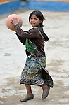 A girl plays basketball during a recess from school in Tuixcajchis, a small Mam-speaking Maya village in Comitancillo, Guatemala.