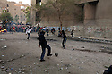 Egyptian protestors defiantly kick around a football despite nearby attacking security forces during street battles November 21, 2011 near Tahrir square  in central Cairo, Egypt. Thousands of protestors demanding the military cede power to a civilian government authority clashed with Egyptian security forces for a third straight day in Cairo, with hundreds injured and at least 24 protestors killed.  (Photo by Scott Nelson)