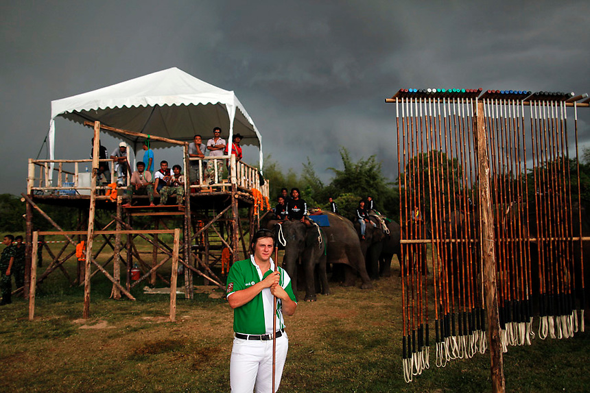 Storm approaches as people watch elephant polo players practicing after the opening parade of the 10th annual King's Cup Elephant Polo Tournament in Hua Hin, nearly 160 km (100 miles) south of Bangkok September 5, 2011. Twelve international teams ride Thai street elephants during the week-long tournament, which will conclude on September 11 with the final.  REUTERS/Damir Sagolj (THAILAND)