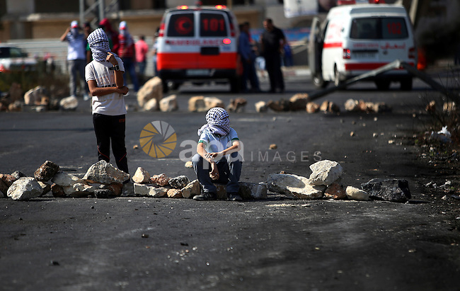 Palestinian protesters take a rest during clashes with Israeli security forces near the Beit El settlement on the outskirts of Ramallah in the West Bank, on October 17, 2015. The unrest that has engulfed Jerusalem and the occupied West Bank, the most serious in years, has claimed the lives of 34 Palestinians and seven Israelis. The tension has been triggered in part by Palestinians' anger over what they see as increased Jewish encroachment on Jerusalem's al-Aqsa mosque compound. Photo by Shadi Hatem