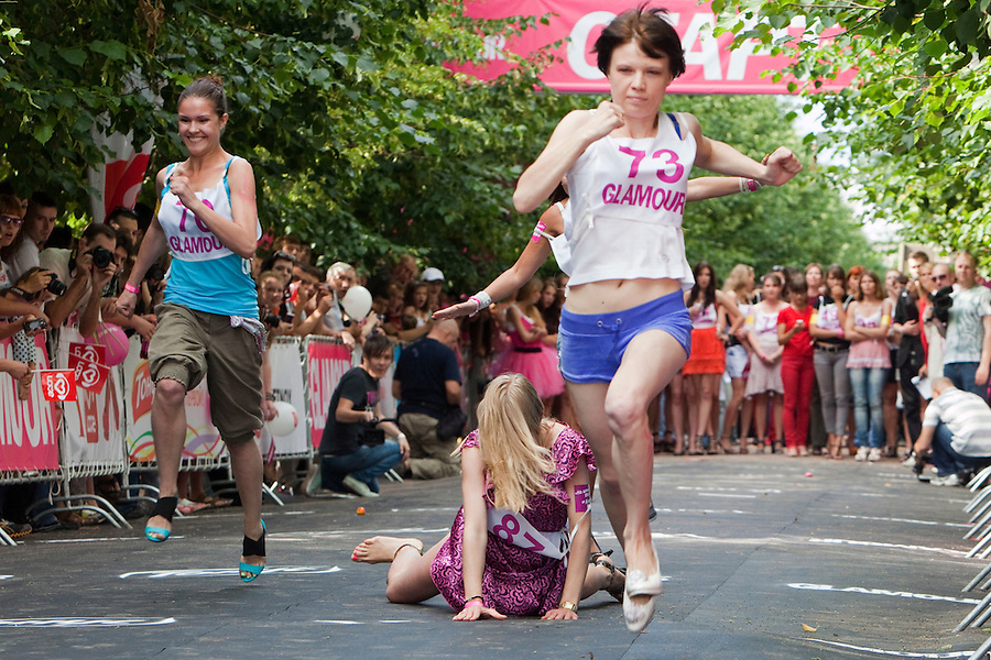 Moscow Russia, 09/07/2011..A contestant trips and falls as her shoe breaks in a High Heel Race competition organised by Russian Glamour magazine in central Moscow. About 100 young women took part in a series of races.