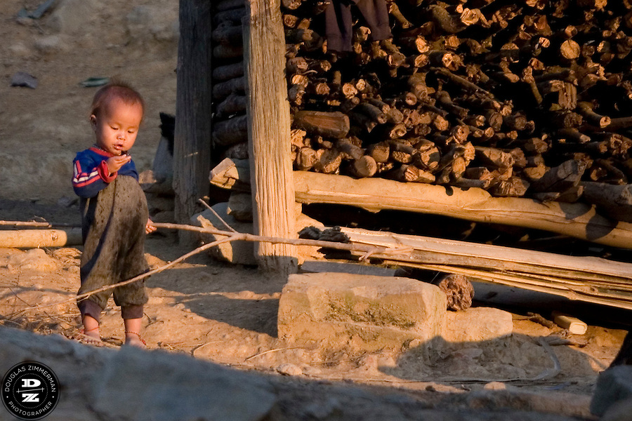 A young child plays in the village of Sam Yord, in the county of Louang Namtha,  Laos.  The remote village, only accessible on foot is a village of the Hmong ethnic group. Photograph by Douglas ZImmerman.