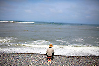 A man sits on the beach on Sunday, Apr. 5, 2009 in Lima, Peru.