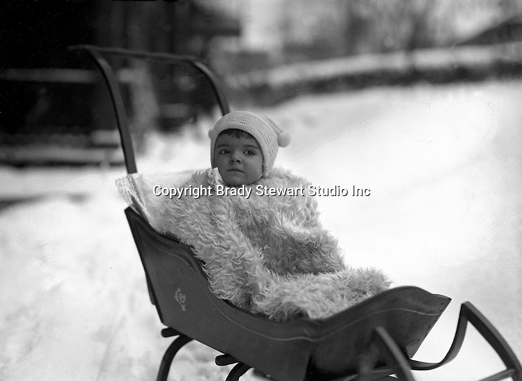 Product: Antique Child's Push Sleigh<br /> <br /> 1917.Wilkinsburg PA: Helen Stewart bundled in a blanket and hat while riding in a baby sleigh - 1917