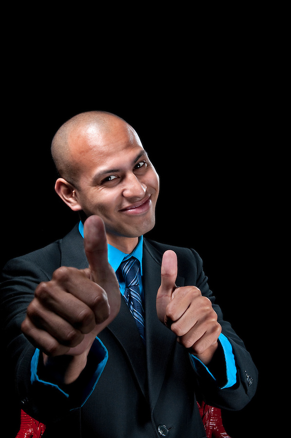 Succesful hispanic businessman gesturing OK with both hands. Use of selective focus. Space for copy.