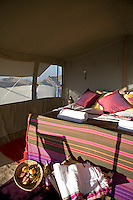 The tent is luxuriously furnished with a comfortable double bed and colouful soft furnishings