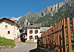 Houses, a fence with red flowers, and the mountains in the background in the town of Stampa, Switzerland where Swiss sculptor Alberto Giacometti was born with the mountains of the Valley Bregaglia in the background