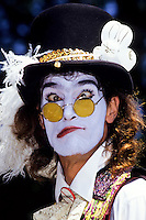 Clown with yellow glasses and bowler hat making faces