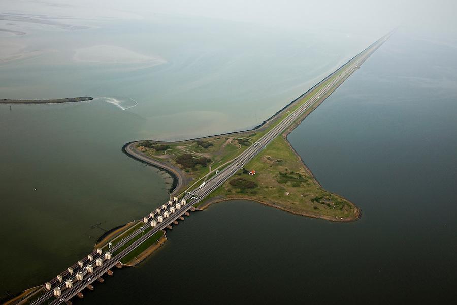 Nederland, Noord-Holland, Gemeente Wieringen, 28-04-2010; Den Oever, begin Afsluitdijk, gezien naar het noordoosten. De dijk vormt de waterkering tussen Waddenzee (li) en IJsselmeer (rechts). In de dijk de Stevinsluizen, spuisluizen of uitwaterende sluizen, het 'eiland' heet Robbenplaat. Aanleg van de dijk vormde onderdeel Zuiderzeewerken, initiatief van ingenieur Cornelis Lely..Den Oever, beginning Enclosure Dam, looking east. The dike forms the barrier between the Wadden Sea (li) and IJsselmeer lake (right). The Stevin sluices sluice surplus water to the Wadden sea. Construction of the dam was part of the Zuiderzee Works, an initiative of engineer Cornelis Lely..luchtfoto (toeslag), aerial photo (additional fee required).foto/photo Siebe Swart