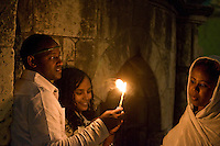 JERUSALEM - APRIL 14 : Ethiopian Orthodox worshipers hold candeles during the Holy fire ceremony at the Ethiopian section of the Holy Sepulcher in Jerusalm Israel on April 14 2012