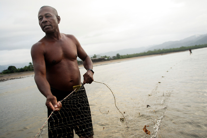 NUQUÍ, EL CHOCO, COLOMBIA -- DECEMBER  11:  Fisherman Ranulpho Asprilla Perea, age 58, checks his nets in Nuquí on December 11, 2005. Nuquí is a small town on Colombia's isolated and untamed Pacific coast, an area sandwiched between endless miles of trackless rainforest and the Pacific Ocean. (Photo by Dennis Drenner/Aurora).