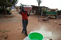 26 September 2011, Alges, Matala, Angola. Women in this community go through a complex process of washing, soaking and rmoving the husks from the maize pips to produce a very white flour that forms their traditional food. A mix is made with a variety of cereals to give it a unique taste.  Canals leading of the Cunene river for irrigation purposes, becomes a lethal channel for the spread of cholera. Households close to the canal use the water for household purposes and open defecation near these water sources, lead to contamination later on. Villages who have erected water tanks and water suply directly to households, are generally protected from the spread of disease. Alges's water tanks supply 2,000 households (approximately 10,000 people).