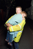 Young girl wrapped in blanket being carried by worker from emergency services. MR
