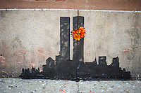 "Street art enthusiasts flock to the Tribeca neighborhood of New York on Tuesday, October 15, 2013 to see the fifteenth installment of Banksy's graffiti art, ""Tribecca"". The elusive street artist is creating works around the city each day during the month of October and this installment shows a silhouette of the World Trade Center with a flower attached.  (© Frances M. Roberts)"