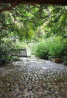 An area of a landscaped garden where a cobbled and paved path leads through a flower garden. Two garden chairs are shaded by a tree and look out over the garden.