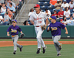 Shortstop Derrik Gibson (18) of the Greenville Drive runs onto the field with two youth ballplayers prior to a game on May 20, 2010, at Fluor Field at the West End in Greenville, S.C.