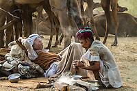Resting camel vendors next to their camels. Pushkar Camel Fair, Rajasthan, India.