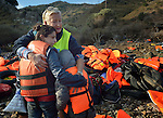 Lisbeth Svendsen, a volunteer from Norway, hugs a frightened Syrian refugee woman and girl on a beach near Molyvos, on the Greek island of Lesbos, on October 30, 2015. The beach behind them is littered with life jackets. The refugees were on a boat that traveled to Lesbos from Turkey, provided by Turkish traffickers to whom the refugees paid huge sums. Svendsen is one of hundreds of volunteers on the island who receive the refugees and provide them with warm clothing and medical care before they continue their journey toward western Europe.