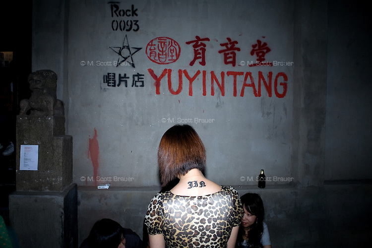 Punk fans wait outside the small YuYinTang rock club in Shanghai, China, between bands.