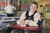 Young boy with Cerebral Palsy sitting in a wheelchair on Children's ward in hospital, smiling and playing with toy car.  MR