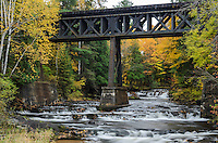An Autumn view of the Falls River with an old, steel train bridge spanning overhead. The waterfall Unnamed Falls can also been seen upstream. L'Anse, MI
