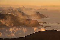 Autumn mist forms over mountains at sunrise from Tønsåsheia, Lofoten Islands, Norway