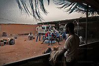 AGADEZ, NIGER &mdash; <br /> Migrants, housed in what is commonly referred to as a &quot;ghetto&quot;, wait for night fall before packing their belongings on the small pick-up trucks that will drive them through the desert on their way to Libya.