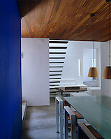 The cobalt blue in the dining area delineates the space in the otherwise white living room