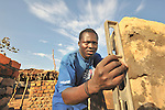 Jackson Batal checks the plumb of a brick wall in the Southern Sudan village of Kupera. Families here are rebuilding their homes after returning from refuge in Uganda in 2006 following the 2005 Comprehensive Peace Agreement between the north and south.