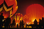 Nighttime hot air balloon glow with crowds of people silhouetted against bright colorful balloons Redmond Washington State USA