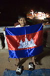 Bunroeun at home with his family, he shows a flag of Cambodia made by his grandmother's factory..A Khmer boy learns to play classical violin at the college of Beaux Arts, at the edge of Cambodia's capital, Phnom Penh. He is an orphan and comes from a poor family. His parents died long ago, from AIDS related diseases. He lives with his grandmother and his uncle, and their family. He lives on the top floor of an apartment block, where his family run a textile business, sewing together clothes and ornamental flags from around the world. A dozen young women work in this textile business, and the boy's home space is actually amidst this small factory environment which he shares with them. They eat, work and play together like an extended family or community. Phnom Penh, Cambodia