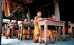 Novice Buddhist monks in Kantabua village, southern Laos, keeping cool in a temple school that has  no walls.