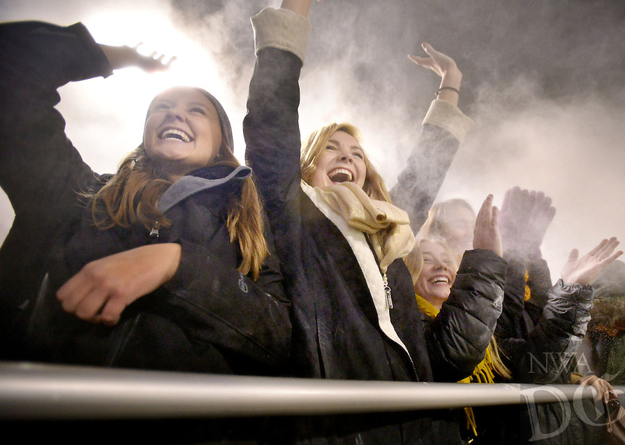 STAFF PHOTO BEN GOFF  @NWABenGoff -- 11/21/14 Sarah Newton, left, and Lydia Fielder, both 17, join the student section in their pre game ritual of throwing baby powder into the air as players take the field before the class 7A playoffs game in Bentonville's Tiger Stadium on Friday Nov. 21, 2014.