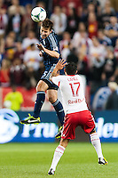 Matt Besler (5) of Sporting Kansas City heads the ball over Tim Cahill (17) of the New York Red Bulls. Sporting Kansas City defeated the New York Red Bulls 1-0 during a Major League Soccer (MLS) match at Red Bull Arena in Harrison, NJ, on April 17, 2013.
