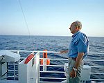 Older Greek man on the deck of a ship in the Greek Islands, Greece
