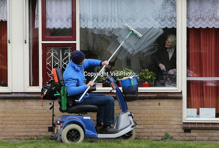 Foto: VidiPhoto..HERVELD - De kersverse invalide glazenwasser Rinke Glas uit het Betuwse Slijk-Ewijk maakt donderdag de ramen van verzorgingshuis de Hoge Hof in Herveld schoon. Het is zijn eerste officiële klus. Hij is noodgedwongen de eerste invalide glazenwasser van Nederland. Per 1 april 2013 worden chronisch zieken en gehandicapten verplicht -waar mogelijk- voor een belangrijk deel in hun eigen onderhoud te voorzien. Hoewel Glas door omstandigheden niet meer kan lopen en aangewezen is op zijn scootmobiel, raakt hij binnenkort het grootste deel van zijn uitkering kwijt. Zijn invalidenvoertuig is nu ook zijn bedrijfswagen..